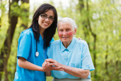 caregiver supporting an elderly woman