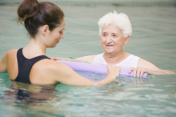 elderly woman in pool with her caregiver